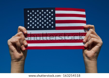 Person holding flag of the United States of Amerida - stock photo