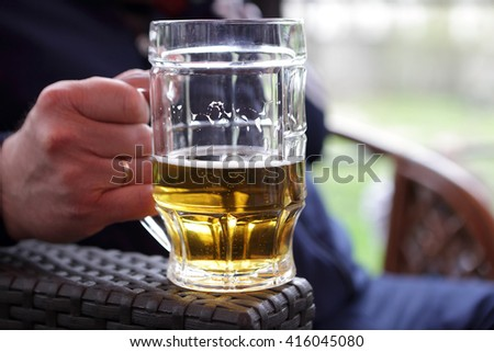 Person holding mug of beer in an outdoor cafe - stock photo