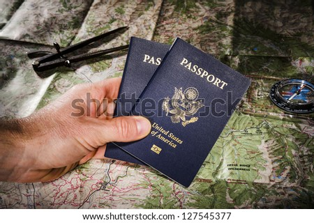 person holding passports with a map and compass in the background