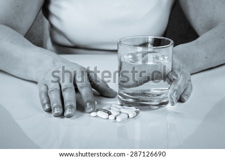person holding pill and glass of water