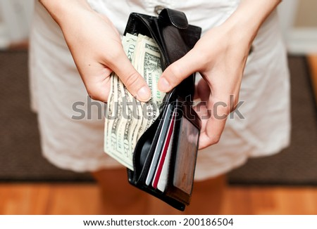 Person holding wallet with money - stock photo