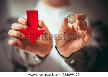 Person holds rouble coin and red arrow. Devaluation of the Russian rouble.  Toned picture