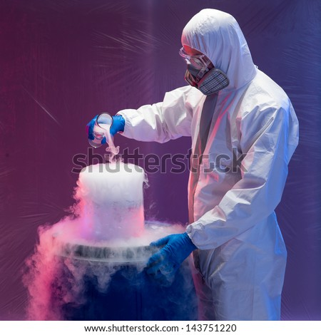 person in a protective suit and gas mask working with steaming substances over a blue waste drum inside a containment tent - stock photo