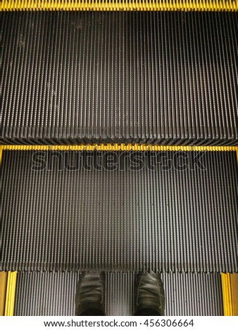 Person in black shoes  going down up the escalator, copy space. - stock photo