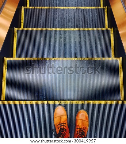 Person in orange boots going down on the escalator.