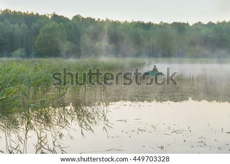 person in the boat rows with oars - stock photo