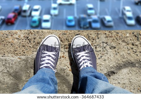 Person in the Jeans and Sneakers on the Edge