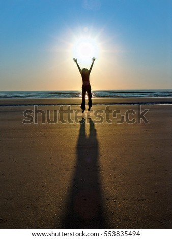 Person jumping in the air, on beach at sunrise
