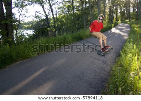 person long boarding down a scenic path - stock photo