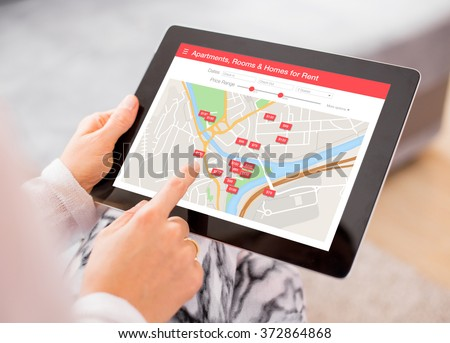 Person looking for places to stay on digital tablet app - stock photo
