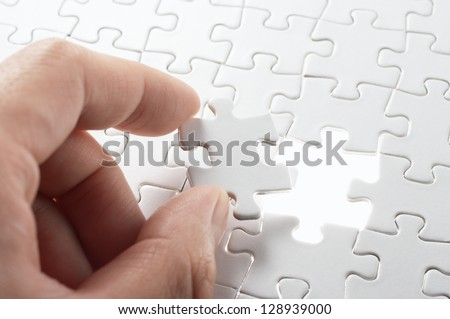 Person matching the last puzzle pieces.Concept image of building and button up. - stock photo