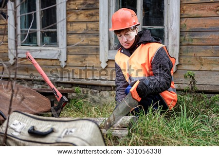 Person of uncertain sex in working clothes sawing a log with a hacksaw.