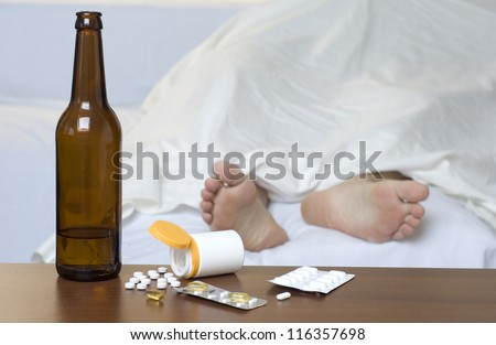 Person passed out in the bed after mixed use of alcohol and drugs. - stock photo