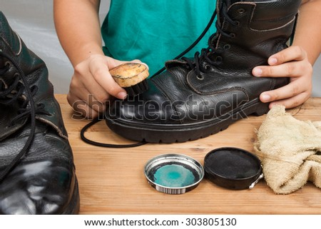 Person polishing a worn out men boots shoe.