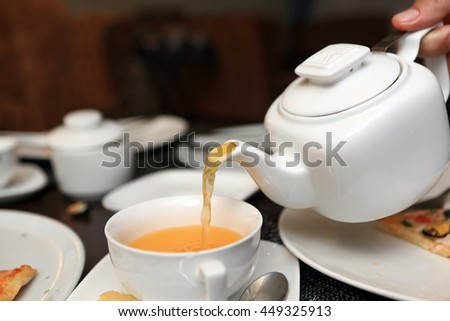Person pouring buckthorn tea in a cafe