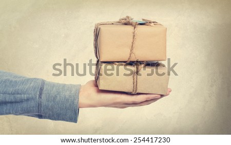 Person presenting vintage style present boxes on muted background - stock photo