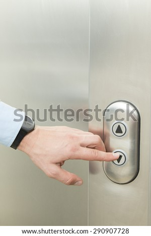 Person pushing down arrow elevator button. - stock photo