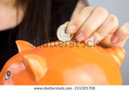 person Putting Coin In Piggy Bank - stock photo
