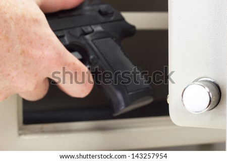 Person putting firearm in gun safe - stock photo