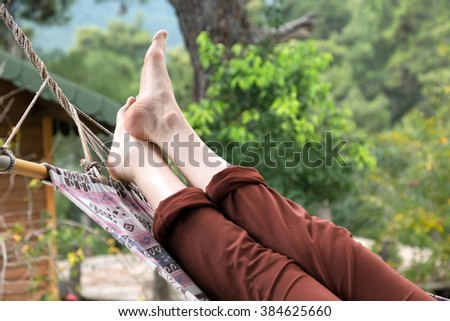 Person relaxing lying in Hammock at rural cottage garden female legs green flora and wooden hut on background - stock photo