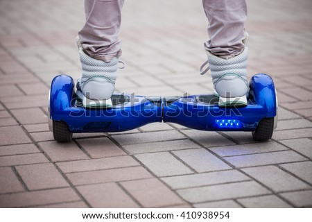 Person riding a modern blue electric mini hover board scooter in outdoors. Popular new city transport that is easy and fun to ride and makes no air pollution to the atmosphere  - stock photo