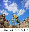 Person riding a mountain bike a mid rocks on a sunny day against a blue sky and clouds, low angle view - stock photo