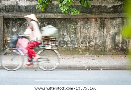 Person riding bicycle on summer day. Old moldy wall with green tree branches. Urban street in Vietnam, Asia. Blurred motion with asian driving bike on road. Woman wearing traditional conical hat. - stock photo