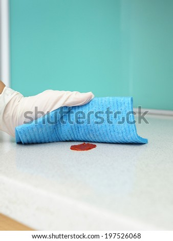 Person's Hand Cleaning Ketchup On Kitchen counter - stock photo