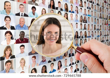 Person's Hand Holding Magnifying Glass Looking At Applicant
