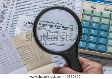 Person's hand holding manifier glass looking at text heading Income tax return empty blank paper form for American residents with blur calculator and bank book record background: USA Tax day concept - stock photo