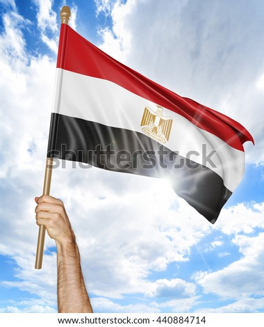 Person's hand holding the Egyptian national flag and waving it in the sky, 3D rendering - stock photo