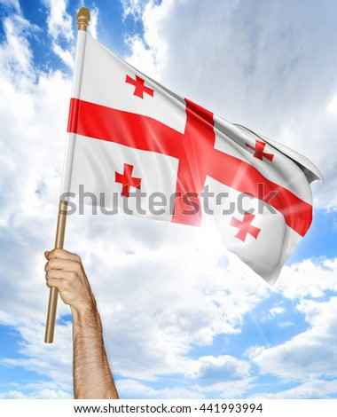 Person's hand holding the Georgian national flag and waving it in the sky, 3D rendering - stock photo