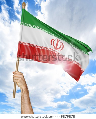 Person's hand holding the Iranian national flag and waving it in the sky, 3D rendering - stock photo