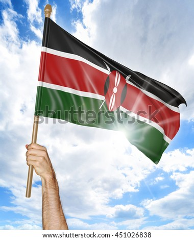 Person's hand holding the Kenya national flag and waving it in the sky, 3D rendering - stock photo