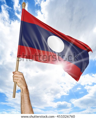 Person's hand holding the Laos national flag and waving it in the sky, 3D rendering - stock photo