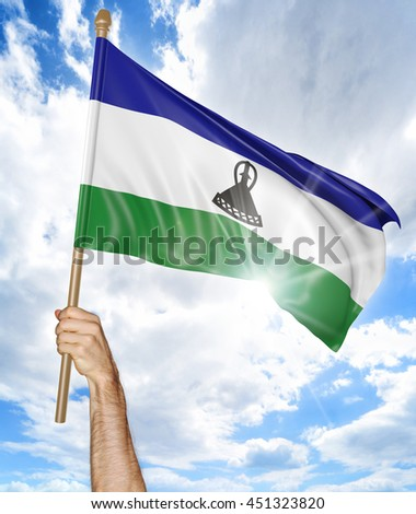 Person's hand holding the Lesotho national flag and waving it in the sky, 3D rendering - stock photo