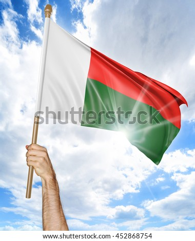 Person's hand holding the Madagascan national flag and waving it in the sky, 3D rendering - stock photo