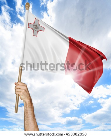 Person's hand holding the Malta national flag and waving it in the sky, 3D rendering - stock photo