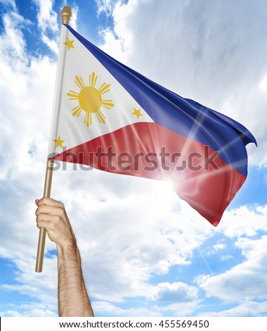 Person's hand holding the Philippines national flag and waving it in the sky, 3D rendering - stock photo