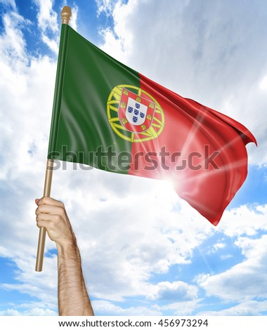 Person's hand holding the Portuguese national flag and waving it in the sky, 3D rendering - stock photo