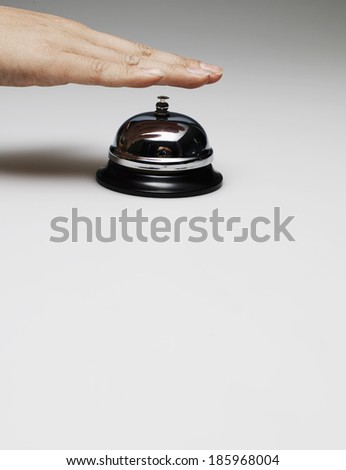 Person's Hand on Desk Bell