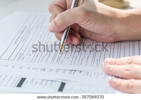 Person's hand with ballpoint pen writing on blank application form paper: Fill in empty document template applying for a job, finance, loan, mortgage or a claim for health, business insurance concept - stock photo