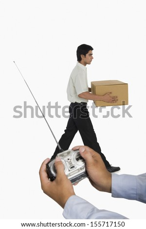 Person's hands controlling a worker with a remote control - stock photo
