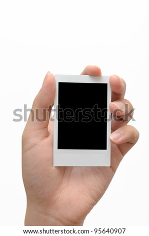 Person's left hand holding instant photo against white background
