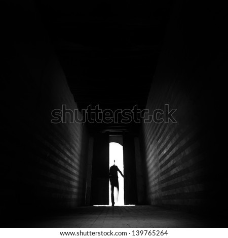 Person's silhouette entering the unknown. - stock photo