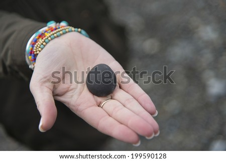 Person showing stone on the palm, Deception Pass State Park, Oak Harbor, Washington State, USA - stock photo