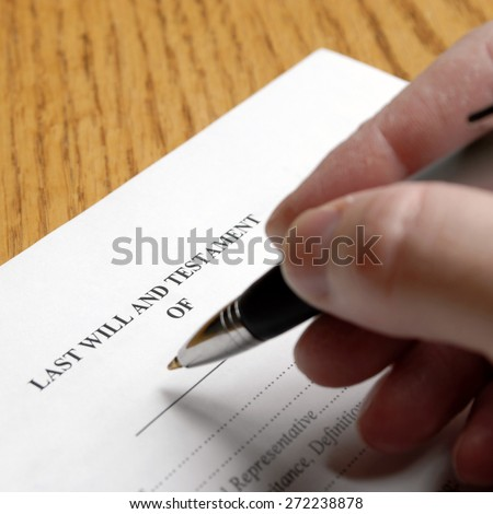 Person signing a will with an elegant pen - stock photo