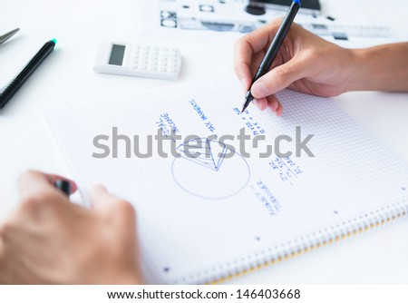 Person sitting at the desk, calculating home earnings and drawing circular diagram with numbers - stock photo