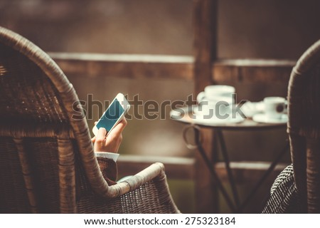 Person sitting in cafe with smartphone in hands. Toned image - stock photo
