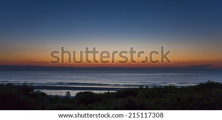 Person sitting In the Lifeguard Chair for the Cape Cod Sunrise.  Taken in Eastham MA,  Coast Guard Beach - stock photo